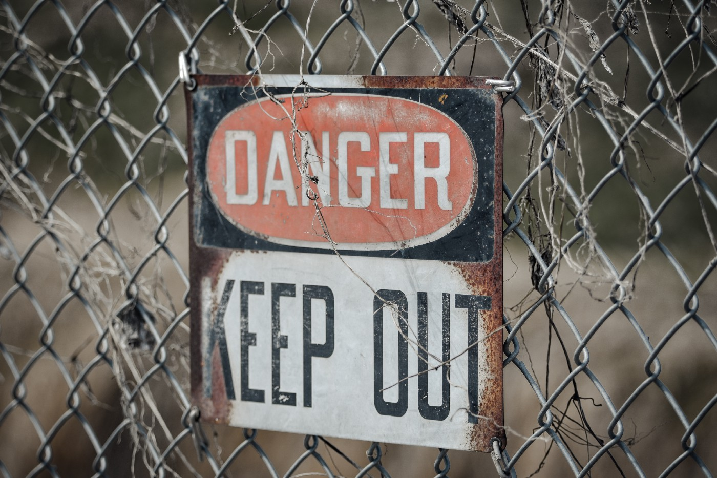 "A sign on a wire fence that says ""DANGER KEEP OUT."""
