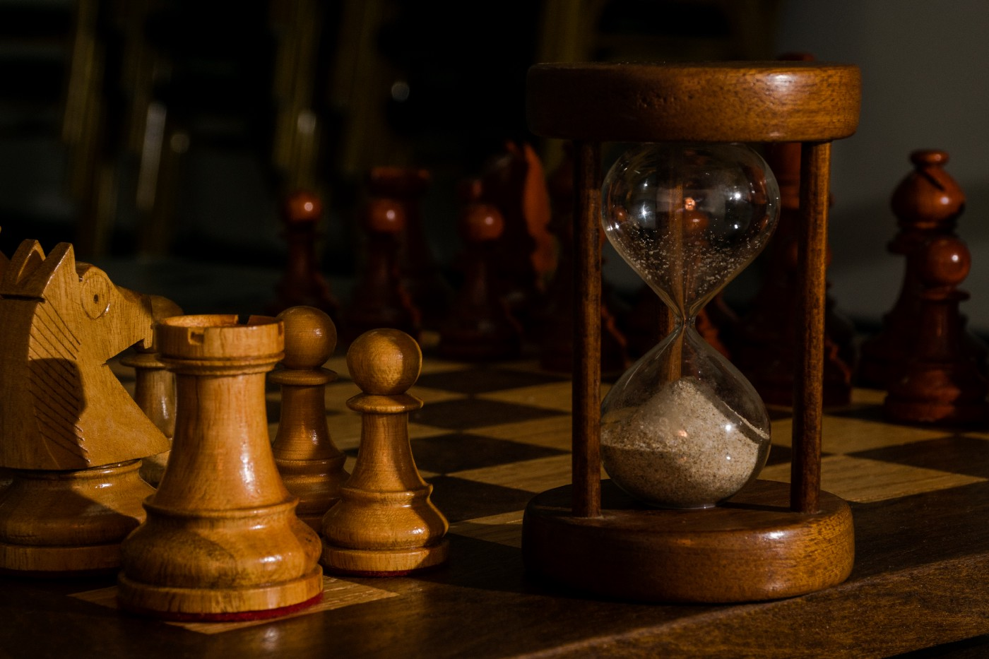 an antique wooden hourglass placed on a chess board with several of the pawns next to it. The pawns are also wooden