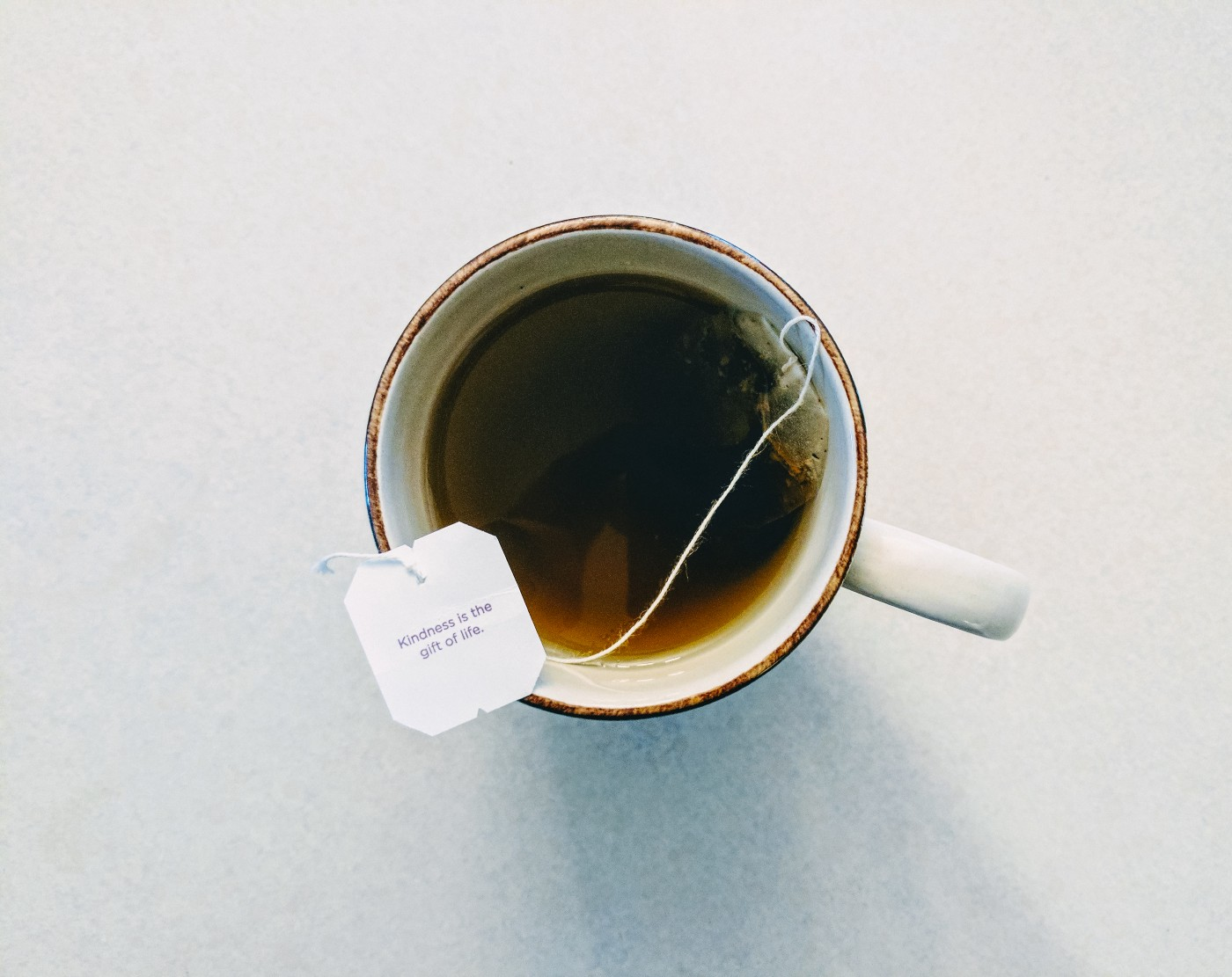 "A mug of tea with a tag that says ""Kindness is the gift of life"""