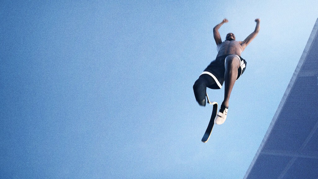 Man with one prosthetic limb jumping in the air with a blue sky above him