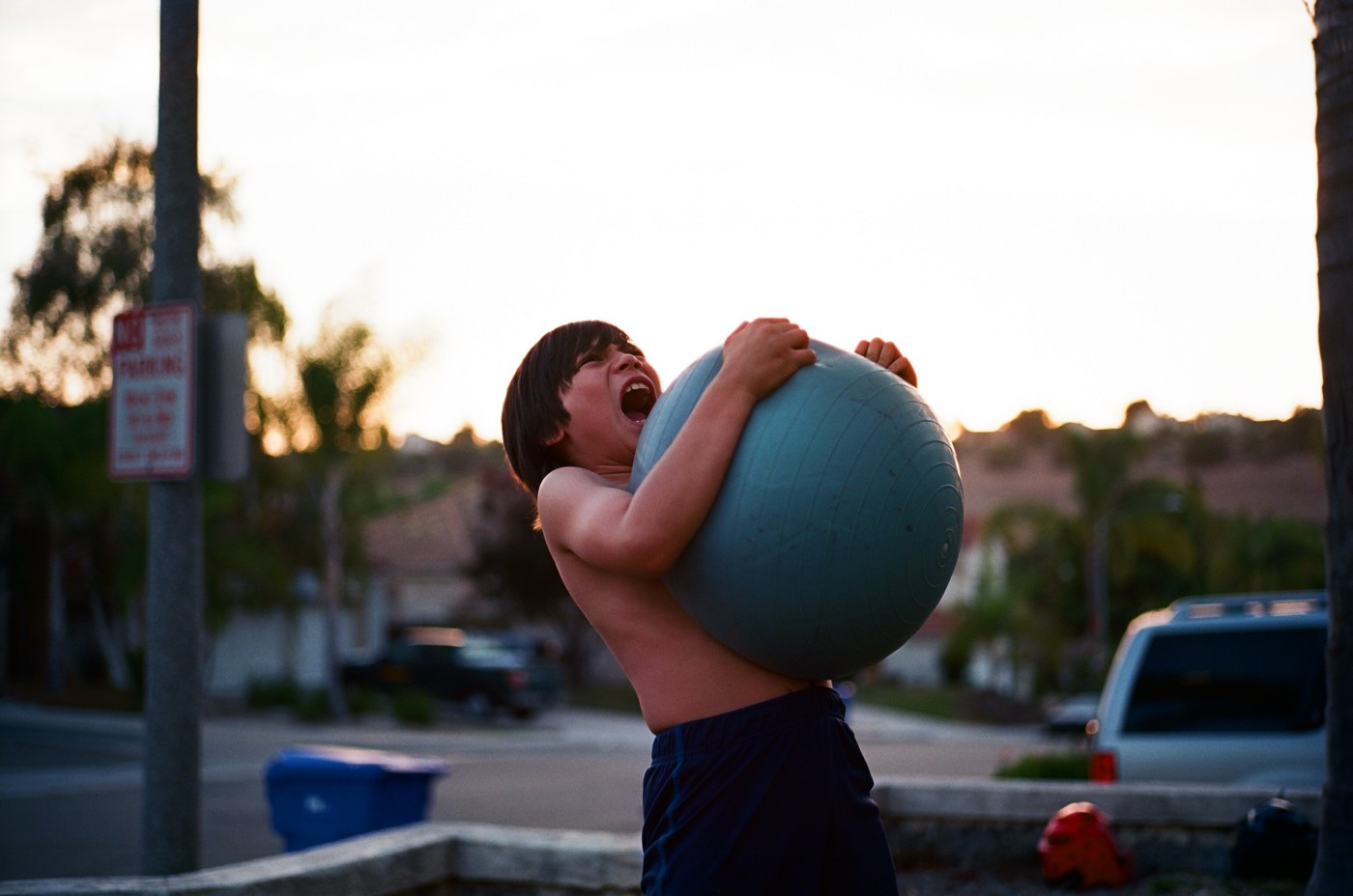 young kid wrestling up a yoga ball in the gym
