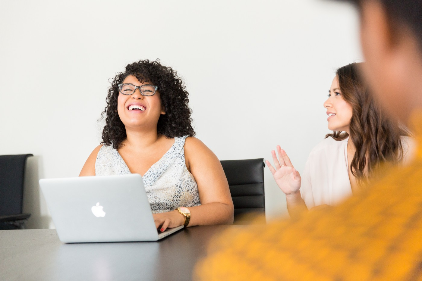 Fun at work. Conference room. One woman types on her MacBook, laughing as her coworker tells an animated story.