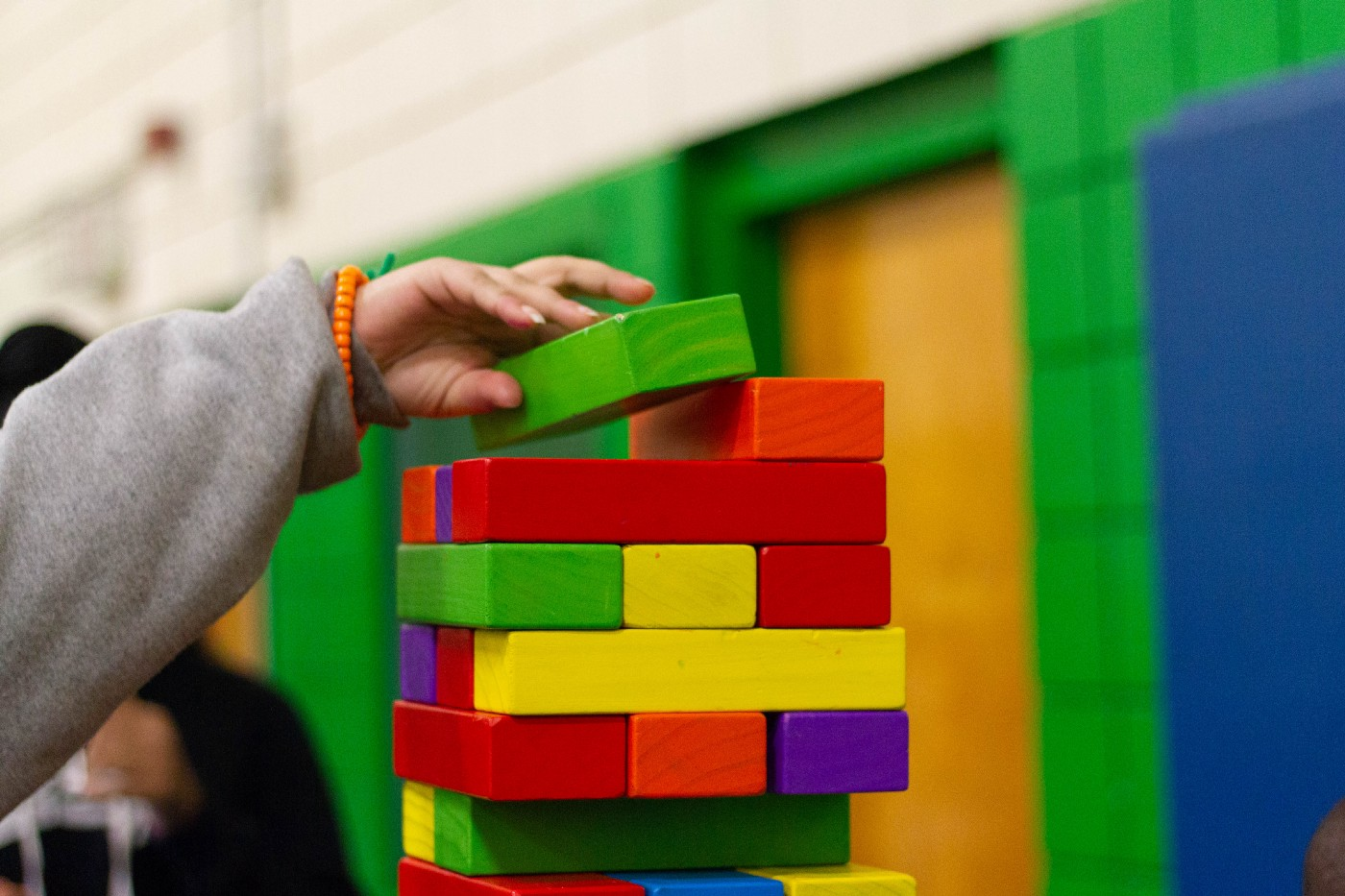Green, red and yellow building blocks. A child adds a green building block to the top of the tower.