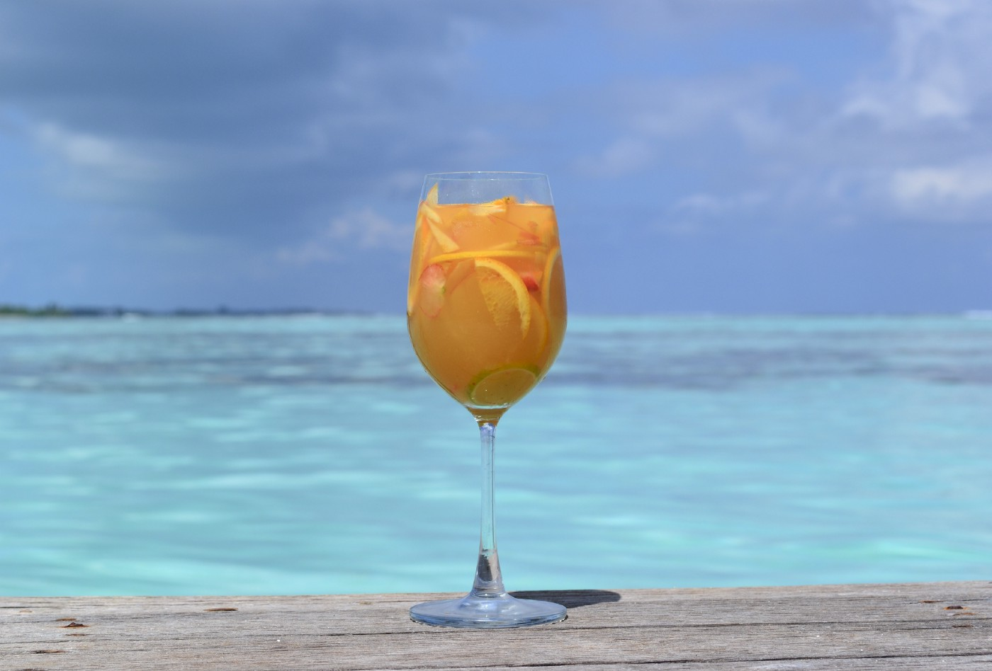 Photo of a fresh juice beverage in a wine glass with an ocean-view in the background
