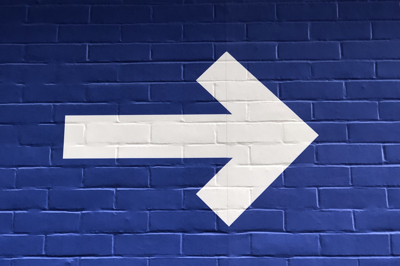A large arrow painted on a brick wall