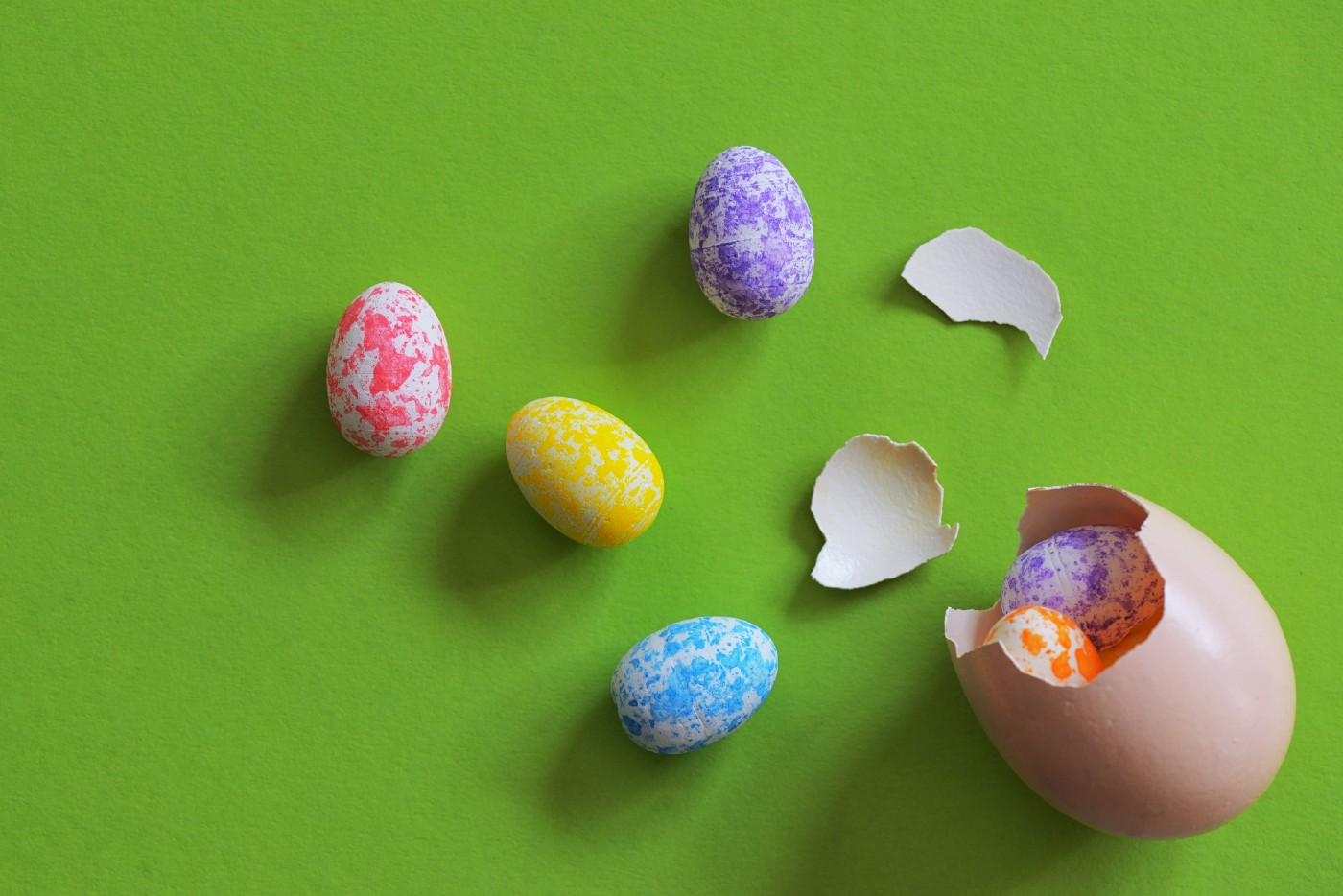 A cracked Easter egg with smaller Easter eggs spilling out of it.