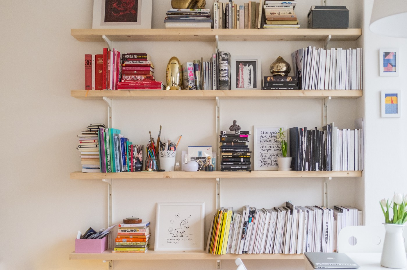 Wall mounted shelves with books sorted by color