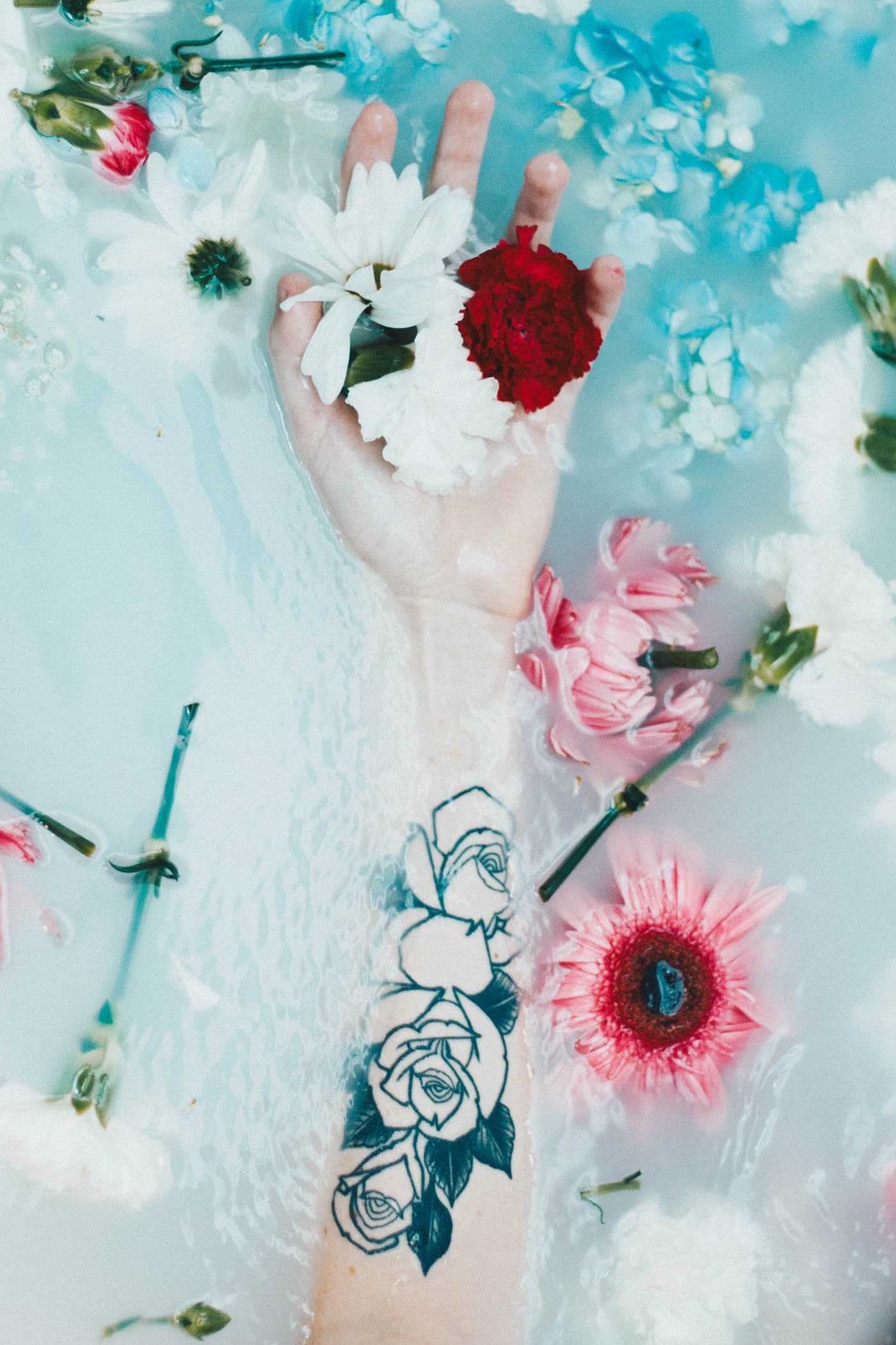 A woman's arm floating in a bathtub full of flower petals.