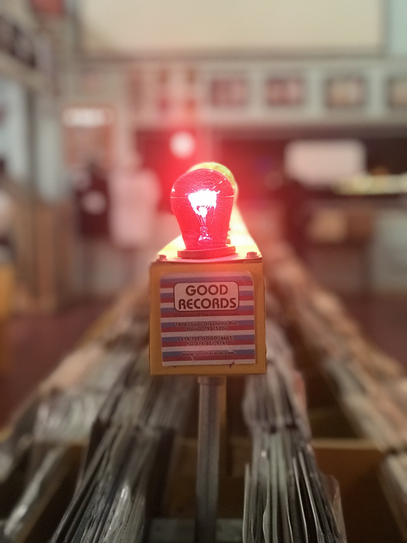 """A red light bulb illuminated above a sign reading """"good records"""""""