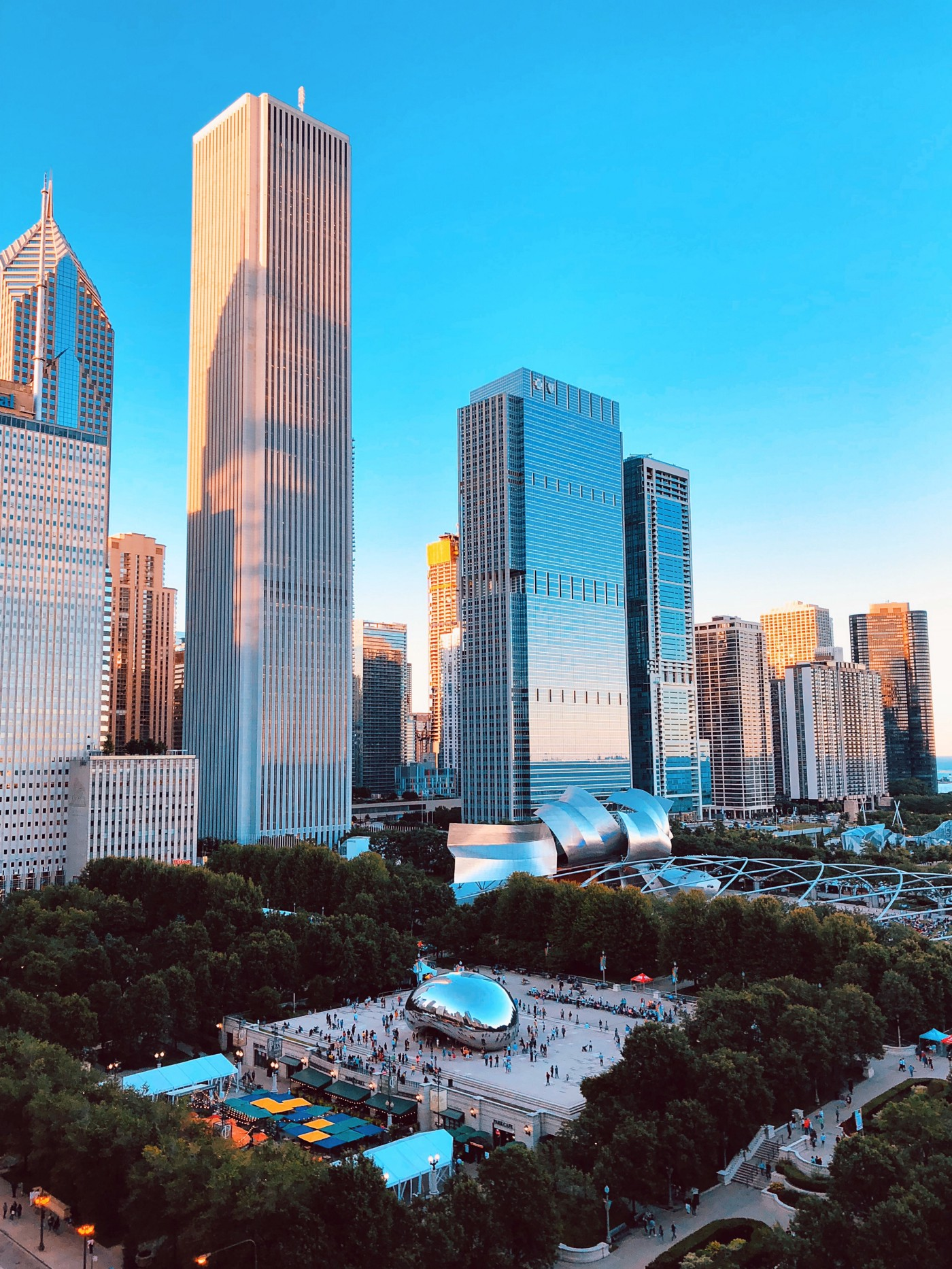 Chicago skyline with view of Millenium Park in the foreground and Aon center behind it. A bright blue sky above.