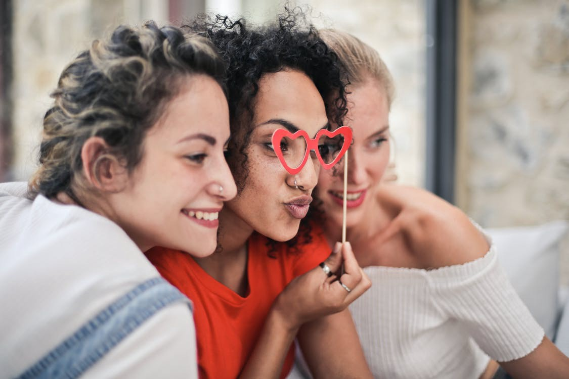 Three friends pose for a photo. The woman in the middle holds cutout heart glasses over her eyes. #galentines #valentines #friends #love