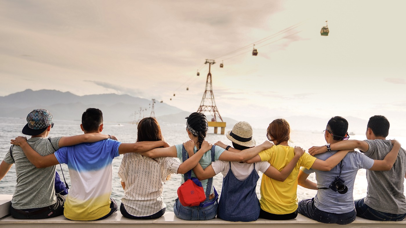 Group of friends, arms in arm, sitting by the sea