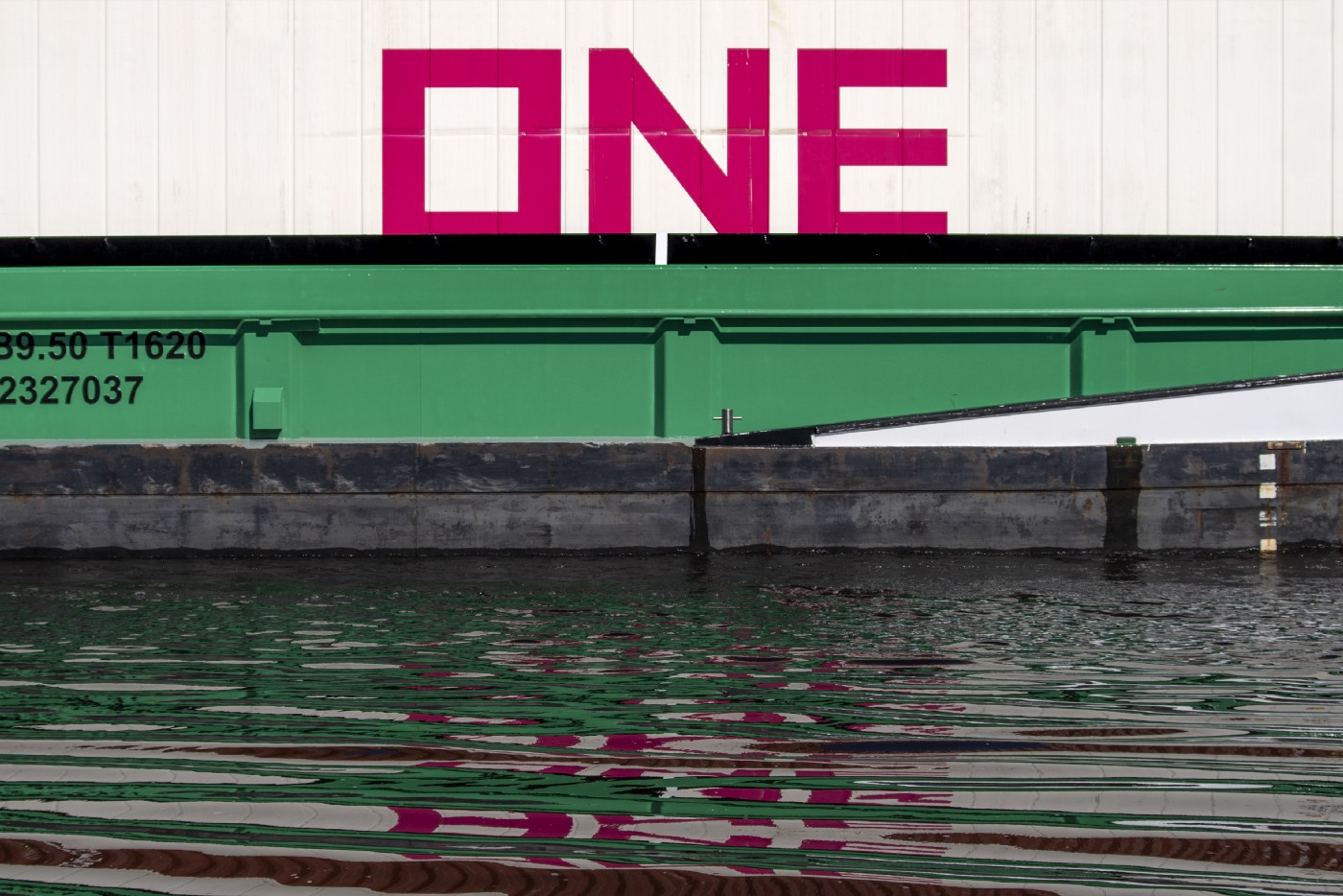 """Huge red letters that spell """"ONE"""" sitting on top of a freight car."""