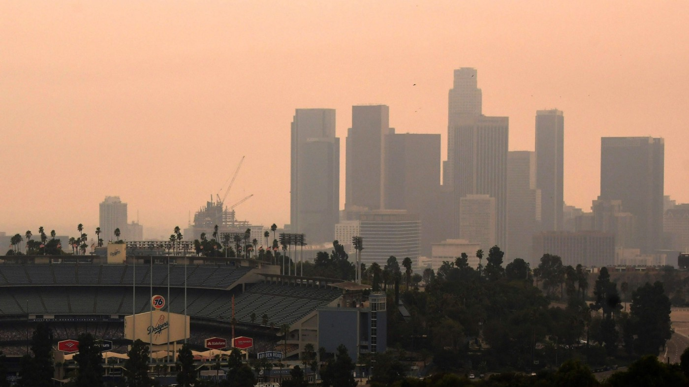 A view of downtown L.A over the shoulder of Dodger Stadium, on a hazy with a peachy orange sky.