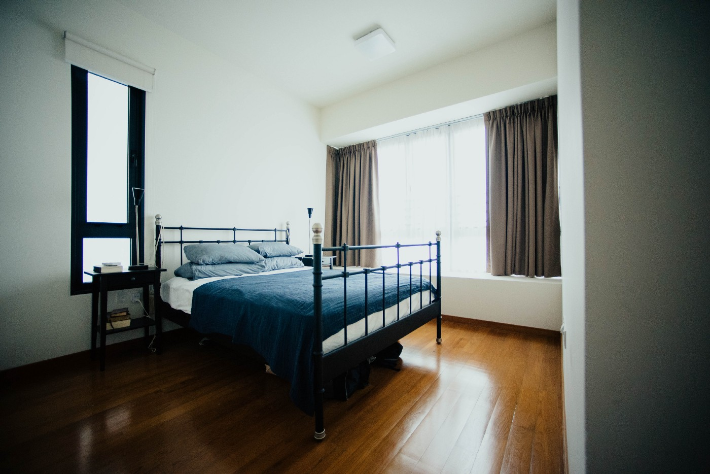 Made queen-sized bed with wrought iron bed frame. sits in clean, sparse bedroom with shiny wood floors and tall windows with sun shining into room. A night stand sits to the right in front of one of the windows.