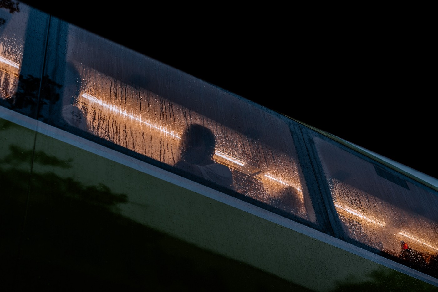 A bus window at night, with the silhouettes of its occupants illuminated by a strip of light inside the cabin.