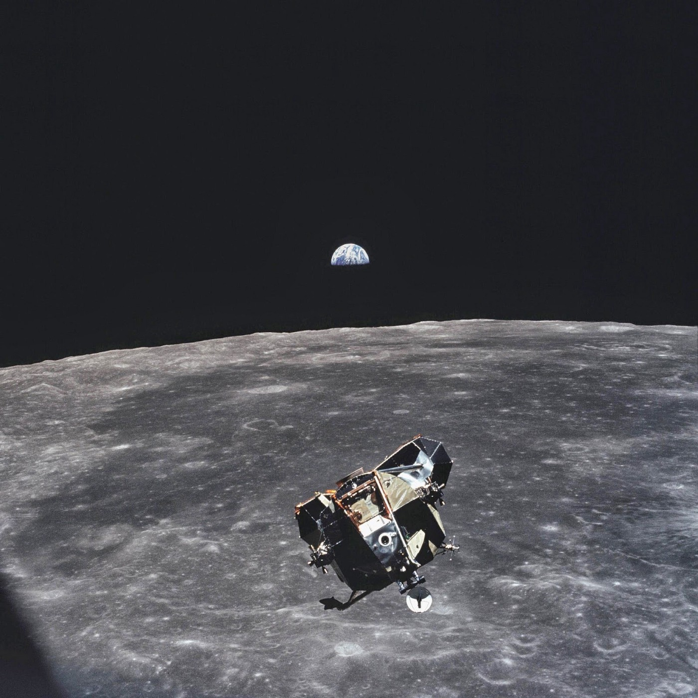 A surface of the moon with a space vehicle on it, and the Earth in the background.