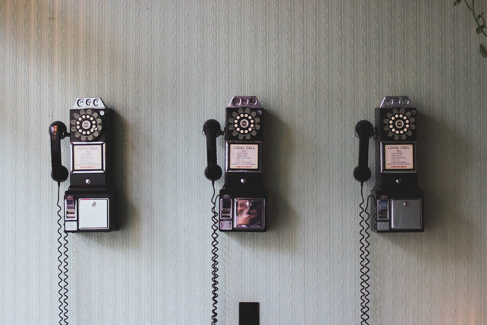 An image of rotary pay phones mounted on a wall