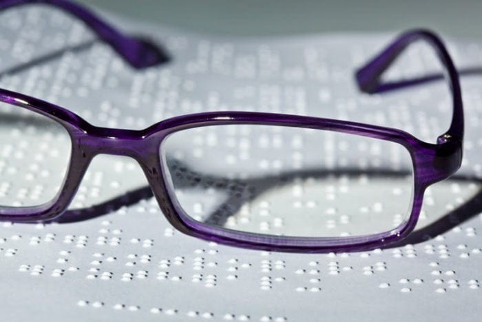 Close-up of embossed braille and a pair of glasses sitting on top