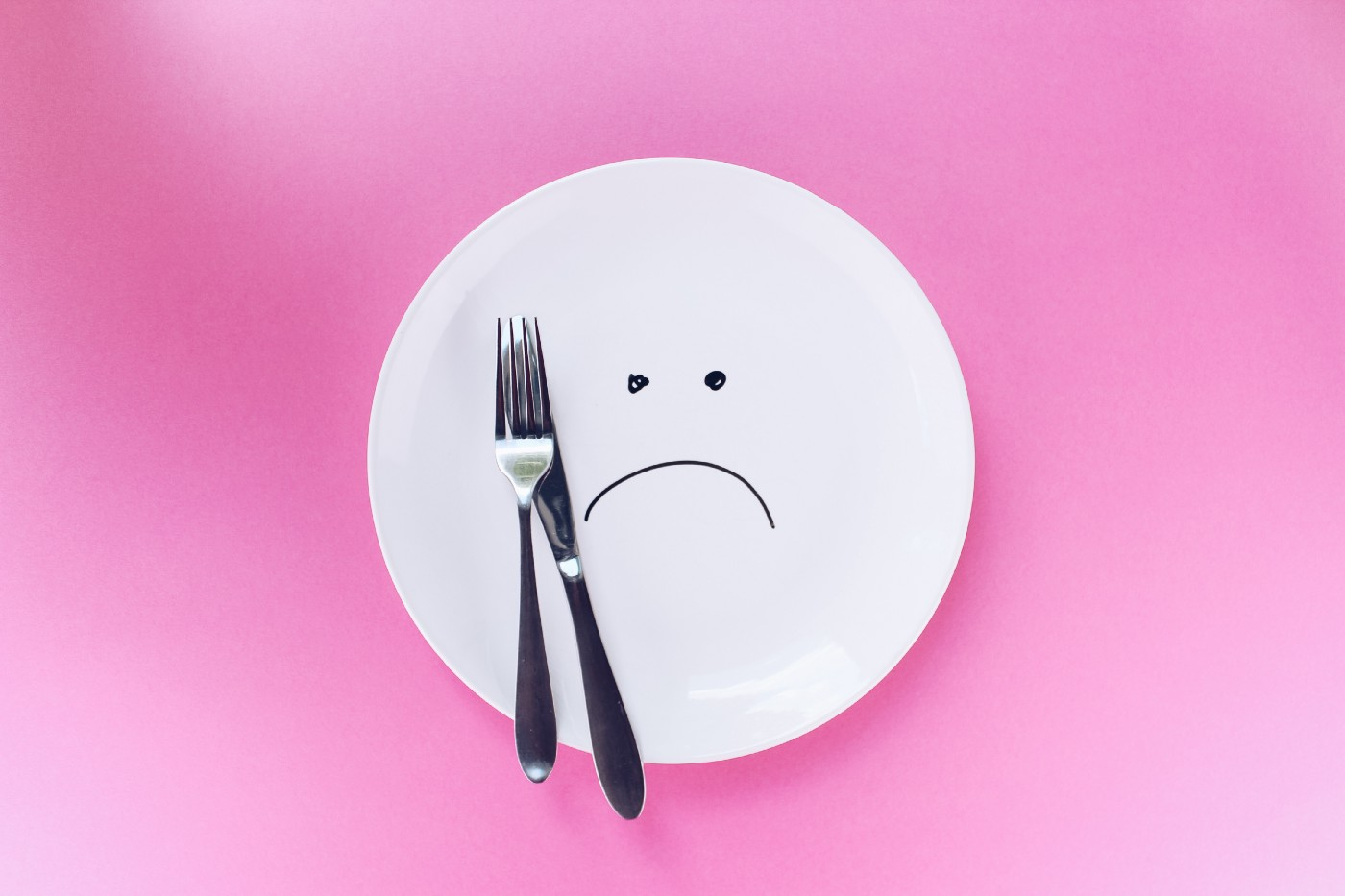 A white plate, with a frown drawn on it, with a fork and knife placed upon it.