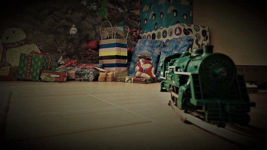 A toy train slightly out of focus in the foreground; in the background, a Christmas tree and presents.