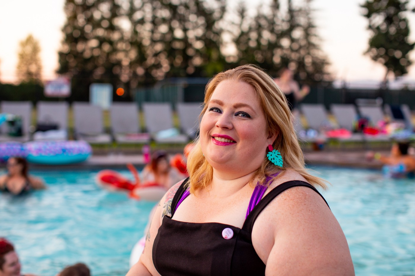 In the foreground is the top half of a fat woman in her thirties who is standing in front of a large in-ground swimming pool. She is wearing a black retro style swimming costume and dangly, bold, aqua colored earrings. Her head is slightly tilted back and she has a gentle smile. In the background people are swimming and sitting on colorful inflatables. The sun is setting and there is a row of beige pool loungers.