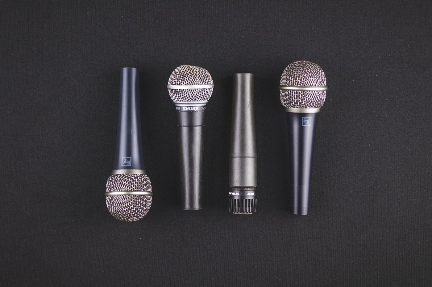 Four microphones on a black background