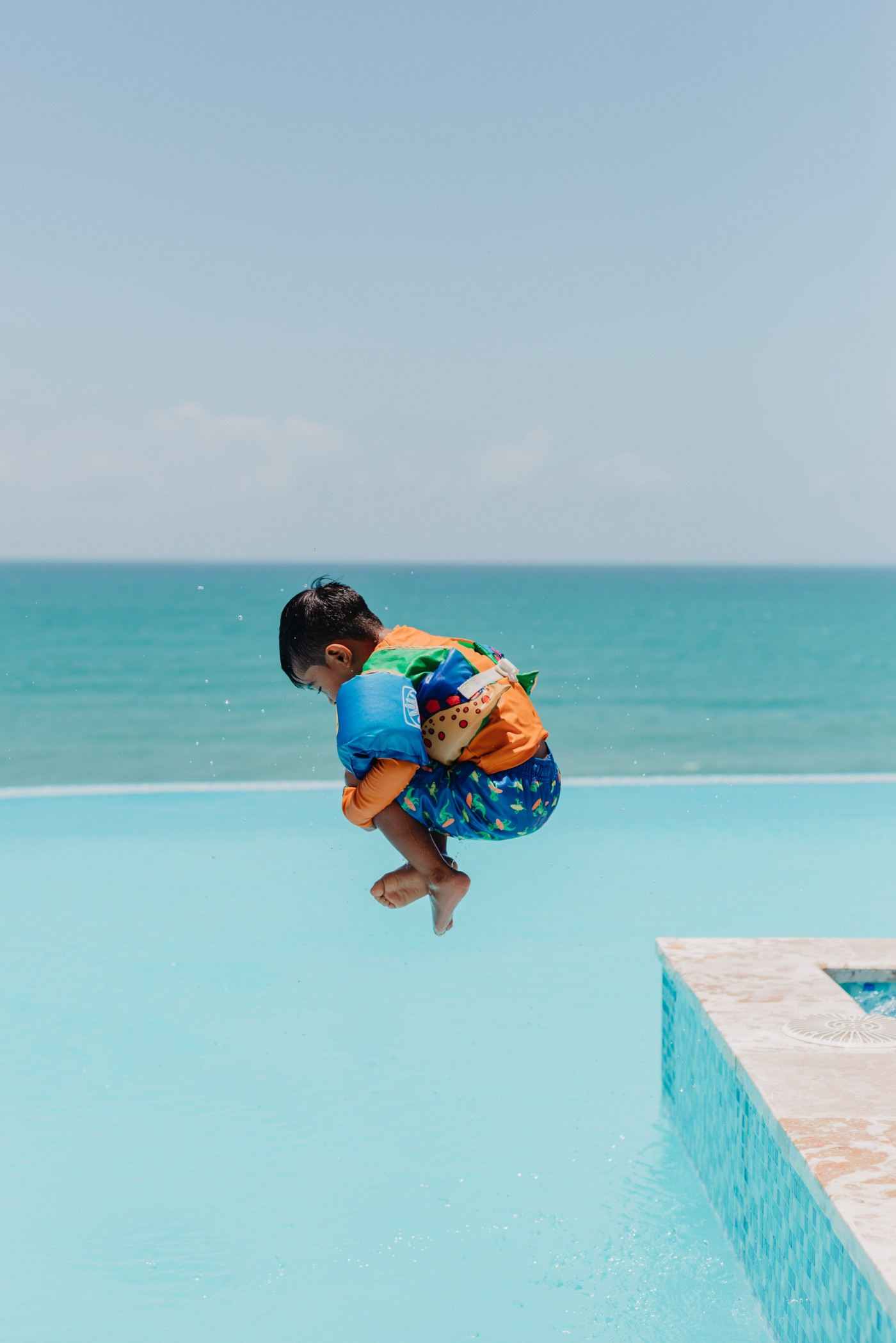 Hi there! BichoDoMato here! This picture displays a kid jumping in a pool, all wrapped on himself (herself?). The green blue of the sea background is stunning and matches well with the blue color of the infinite pool. What a picture! Cheers!