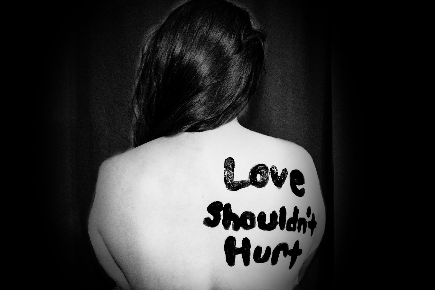 A black and white image of a woman with Love Shouldn't Hurt written in black paint on her bare naked back.