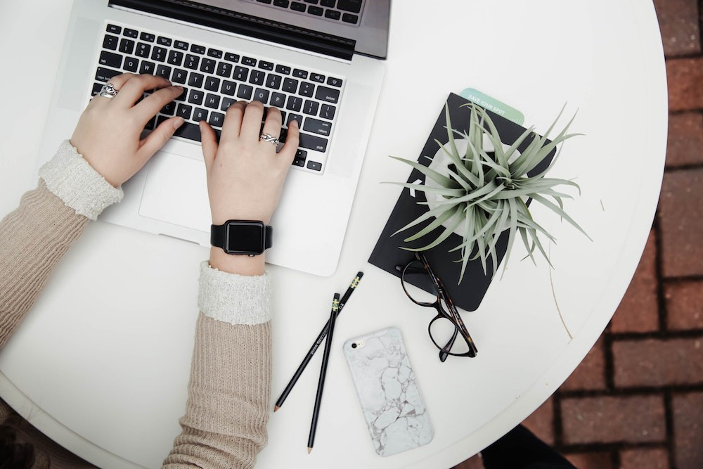 Flatlay of white round table top with laptop, phone, pencil and potted plant, female working on laptop and wearing wristwatch