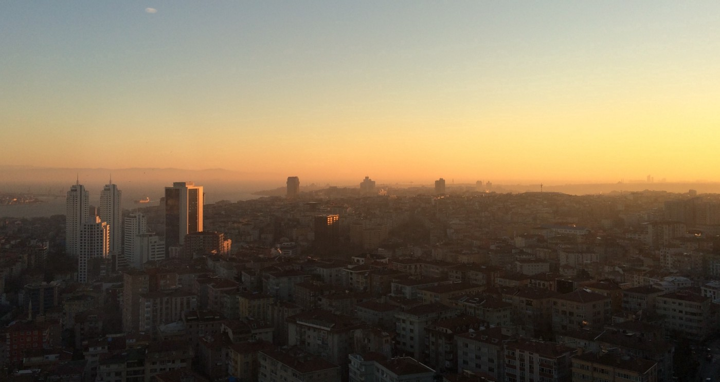 View of cityscape, mostly in shadow. The sun is setting to the right.