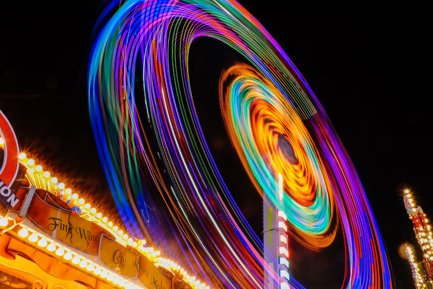spinning wheel of bright neon lights set above a neon sign