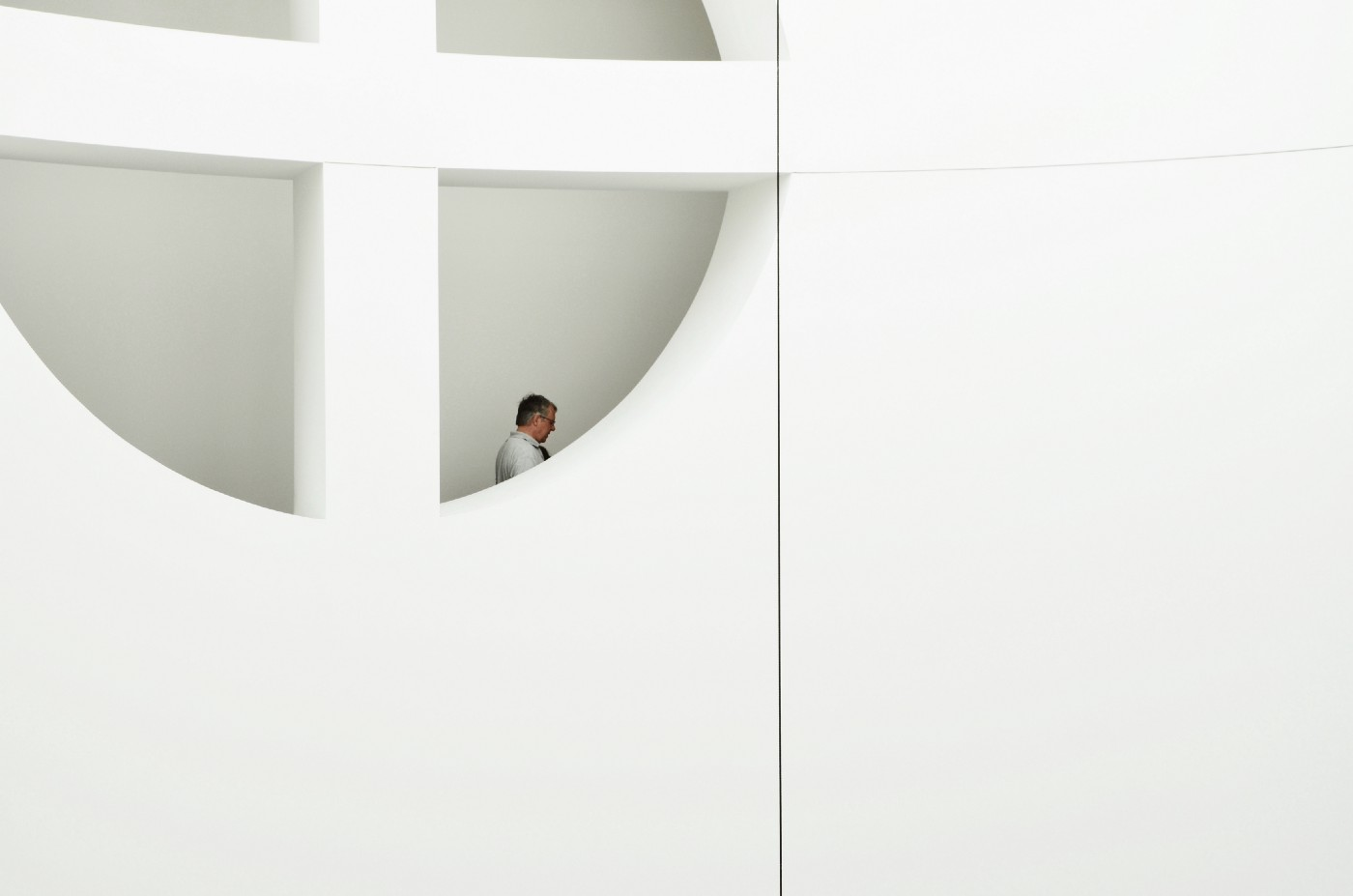 Man standing in near window in white architecture