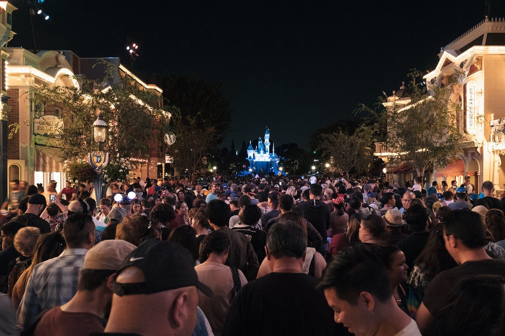 A giant nighttime crowd at the foot of Disneyland's Main St, USA, looking toward the castle. Image: Mike Saechang https://www.flickr.com/photos/saechang/29066900230/ CC BY-ND: https://creativecommons.org/licenses/by-nd/2.0/