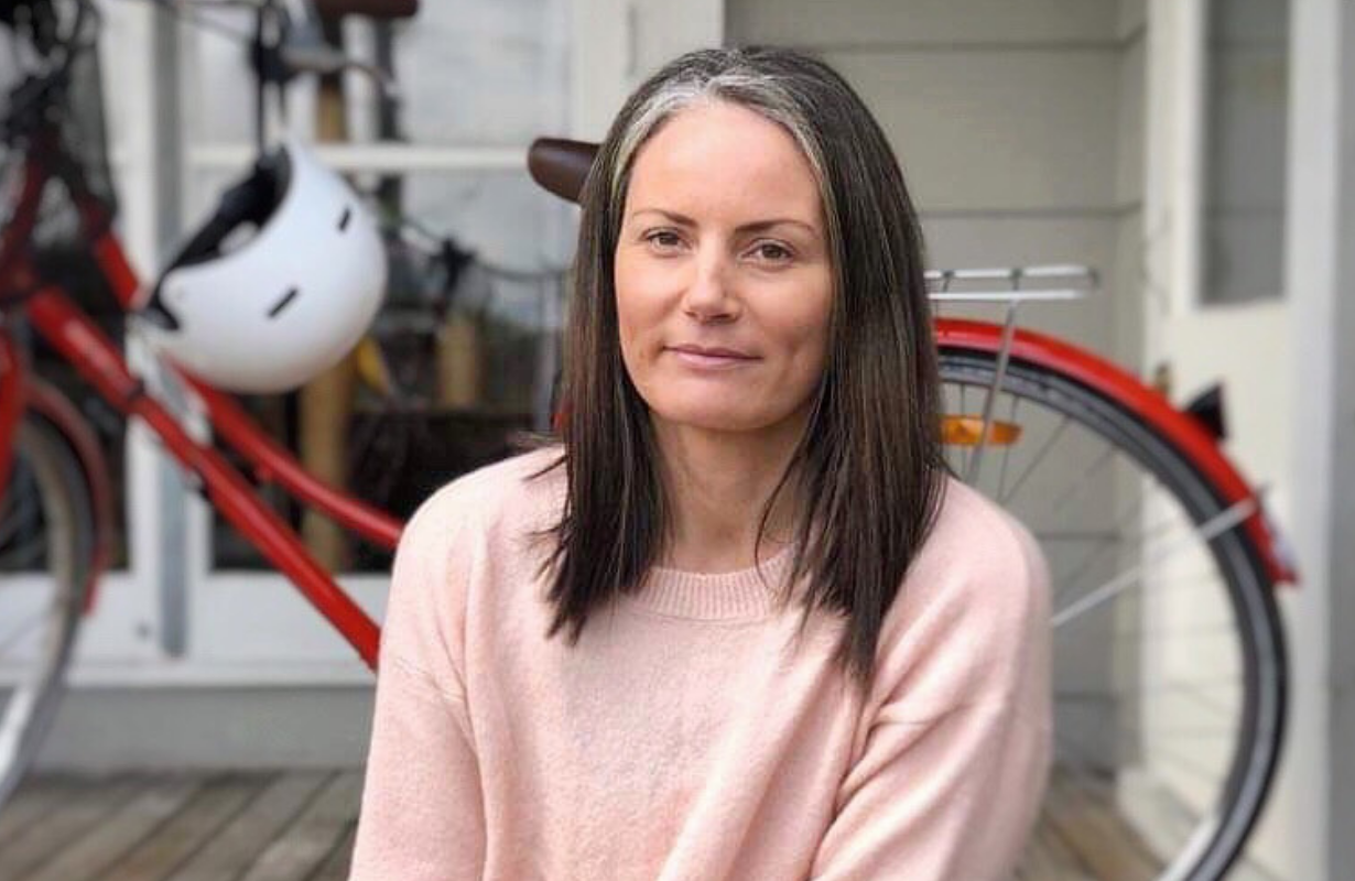 Portrait of Victoria sitting on porch with a red bicycle in the background