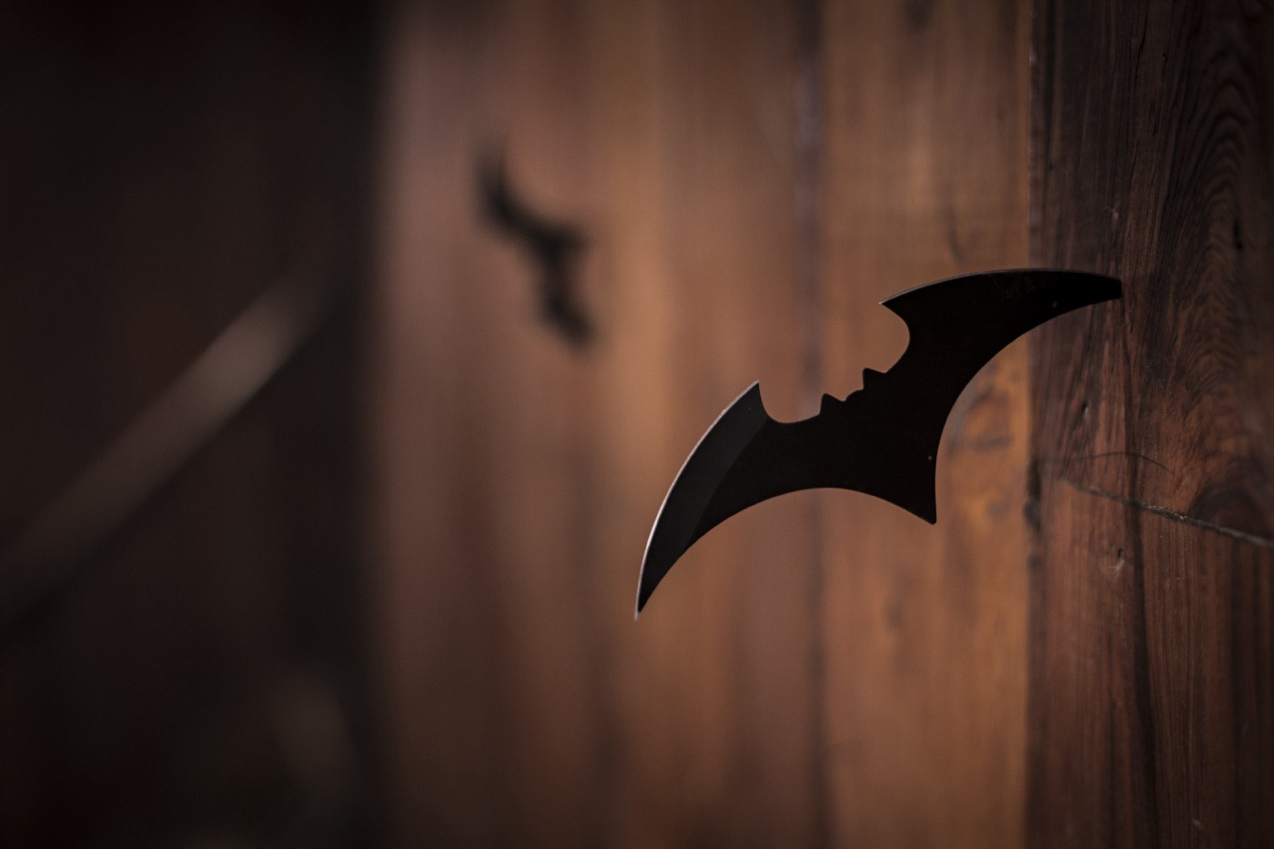 A Batman batarang stuck inside a wooden wall.