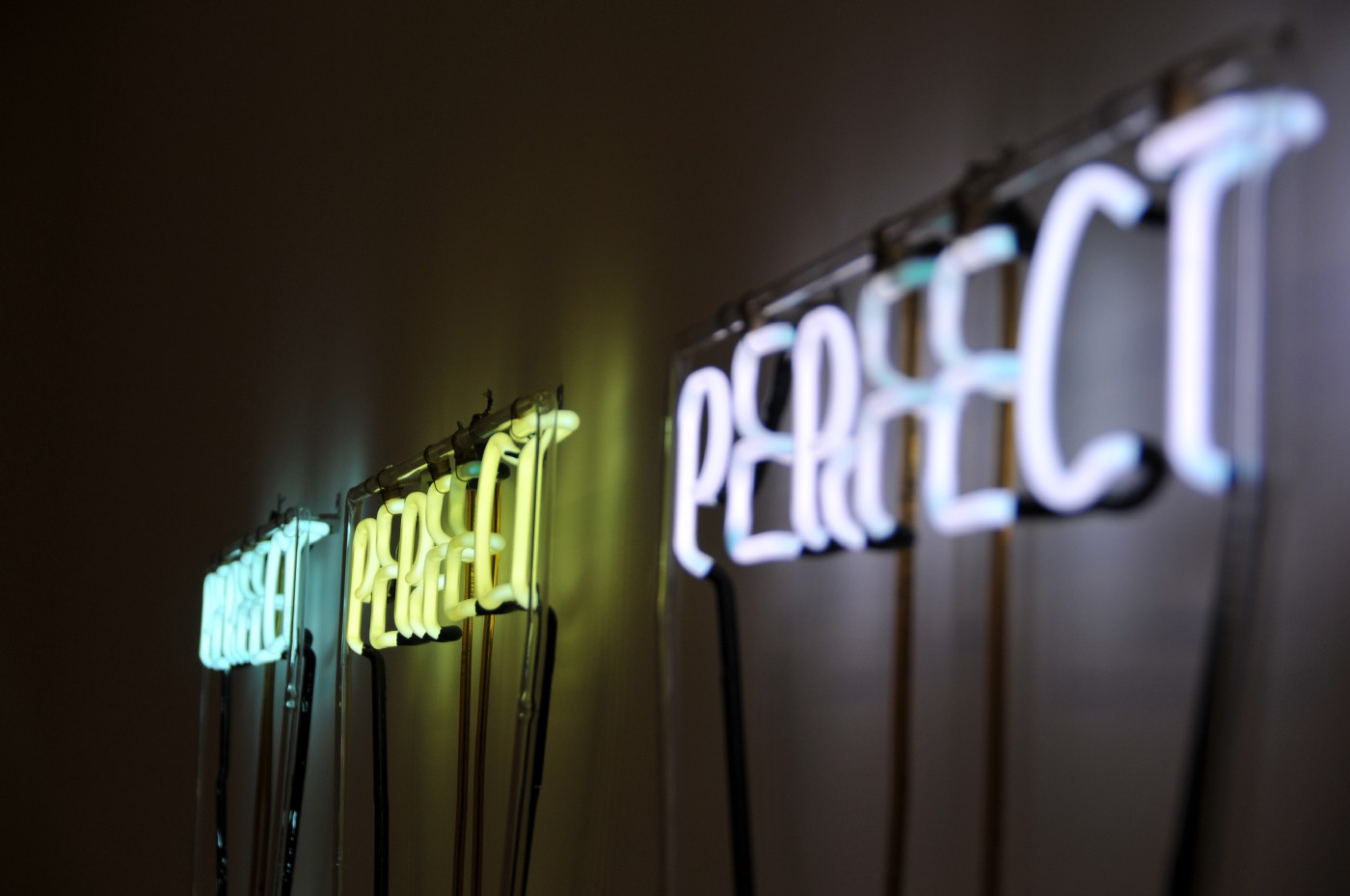 """Three neon signs that spell out """"Perfect"""""""
