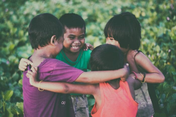 4 children with their arms around each other, laughing and smiling.