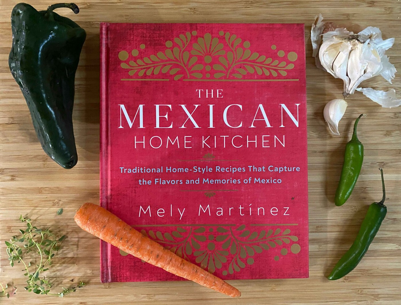 'The Mexican Home Kitchen' cookbook, shown on a bamboo cutting board with fresh chiles, garlic, thyme and a carrot