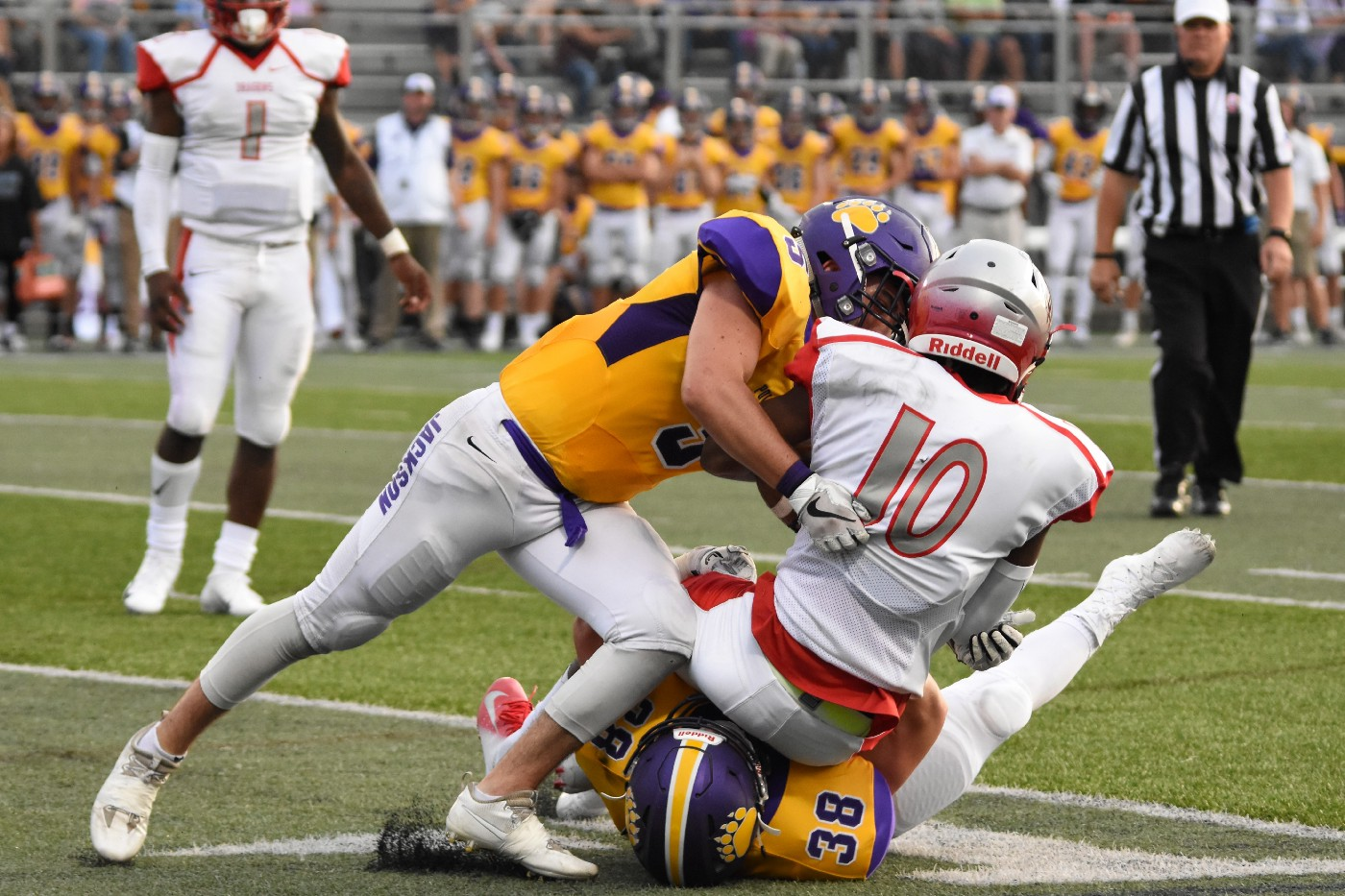 Football player tackles another on the field.