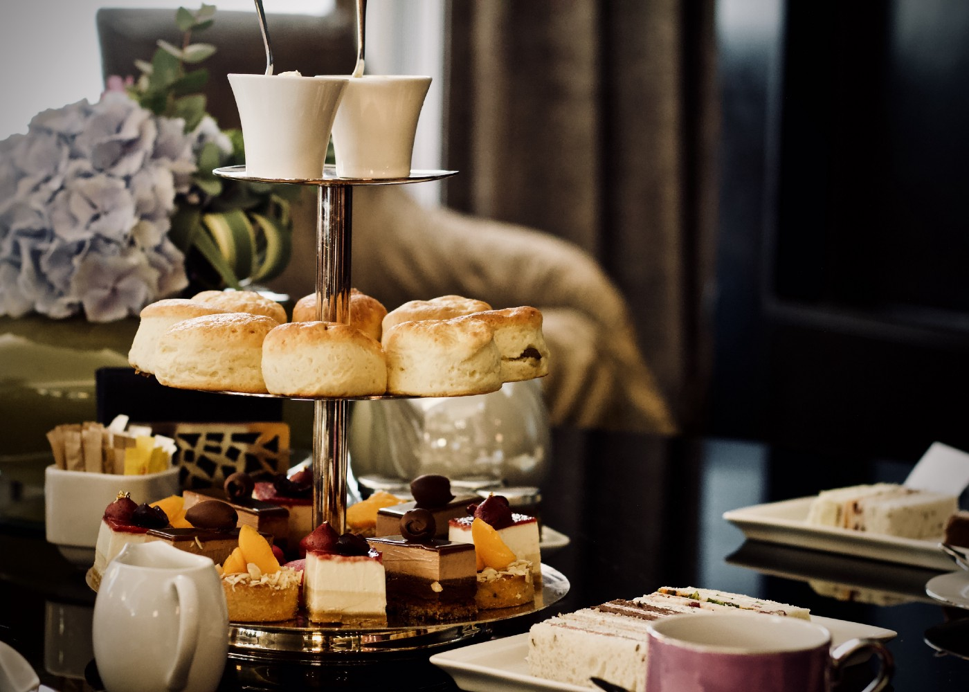 Tea time in England with a tiered platter full of scones.