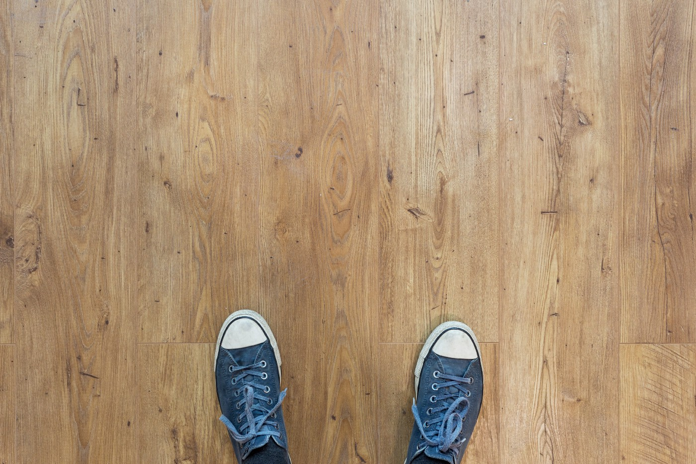 Two blue shoes on a light brown hard wood floor.