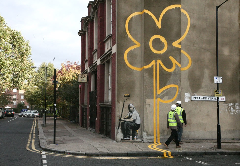 Banksy's Graffiti extends the double yellow lines from the roadway, across the footpath and up the wall to become a flower.
