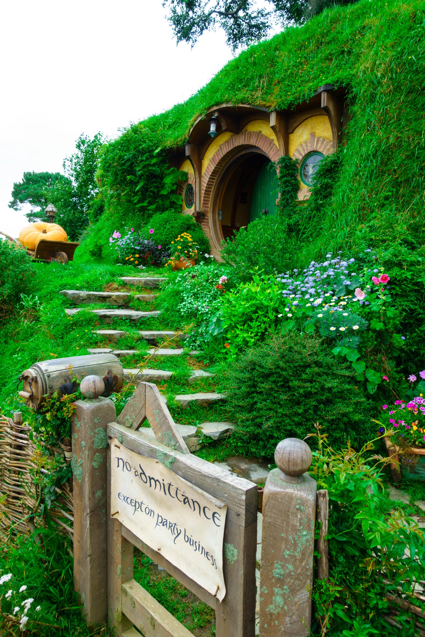 """The Baggins' Hobbit hole. Lush green garden, iconic round wooden door. Sign out front reads: """"No admittance, Except on party business"""""""