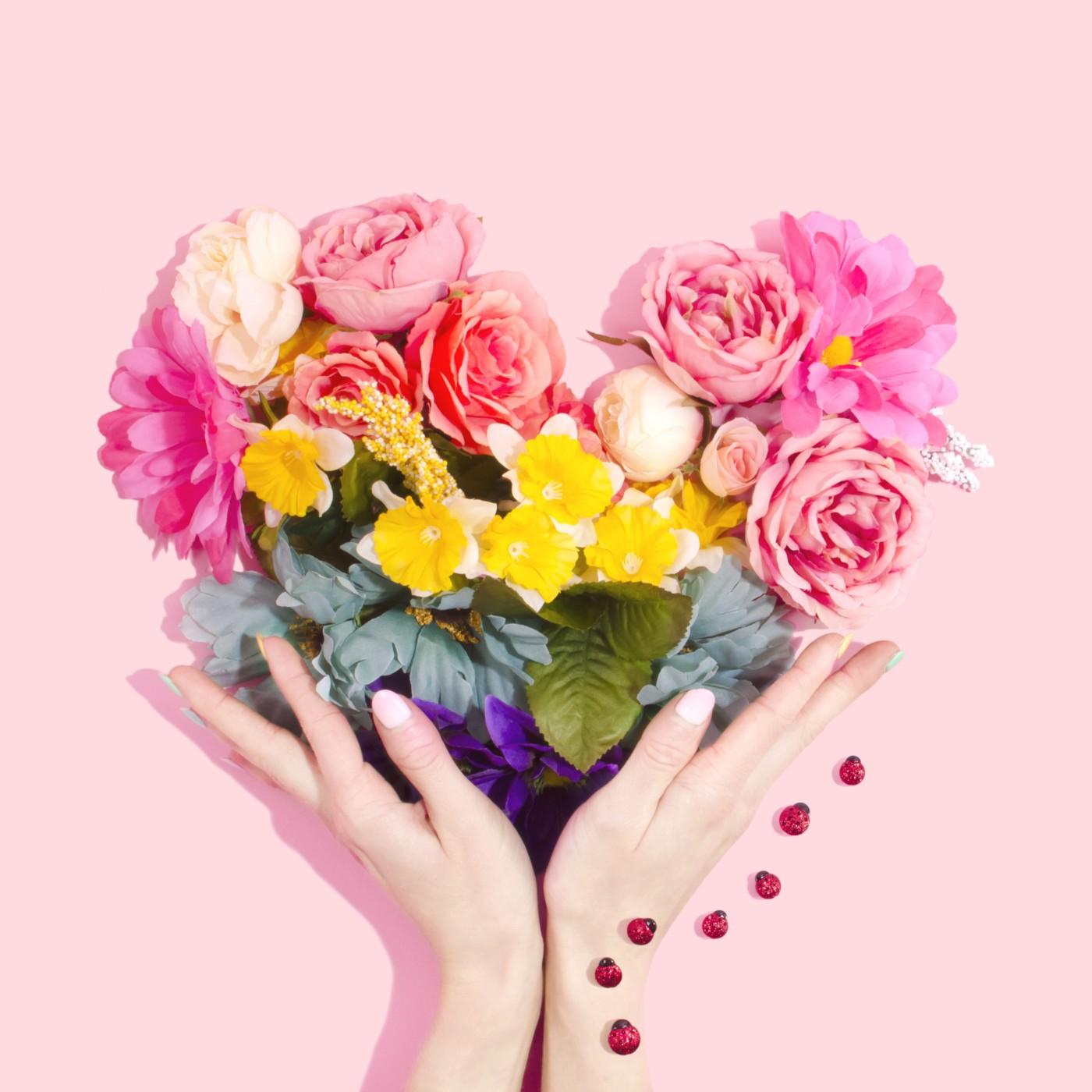 Flowers in heart shape form under a pink background