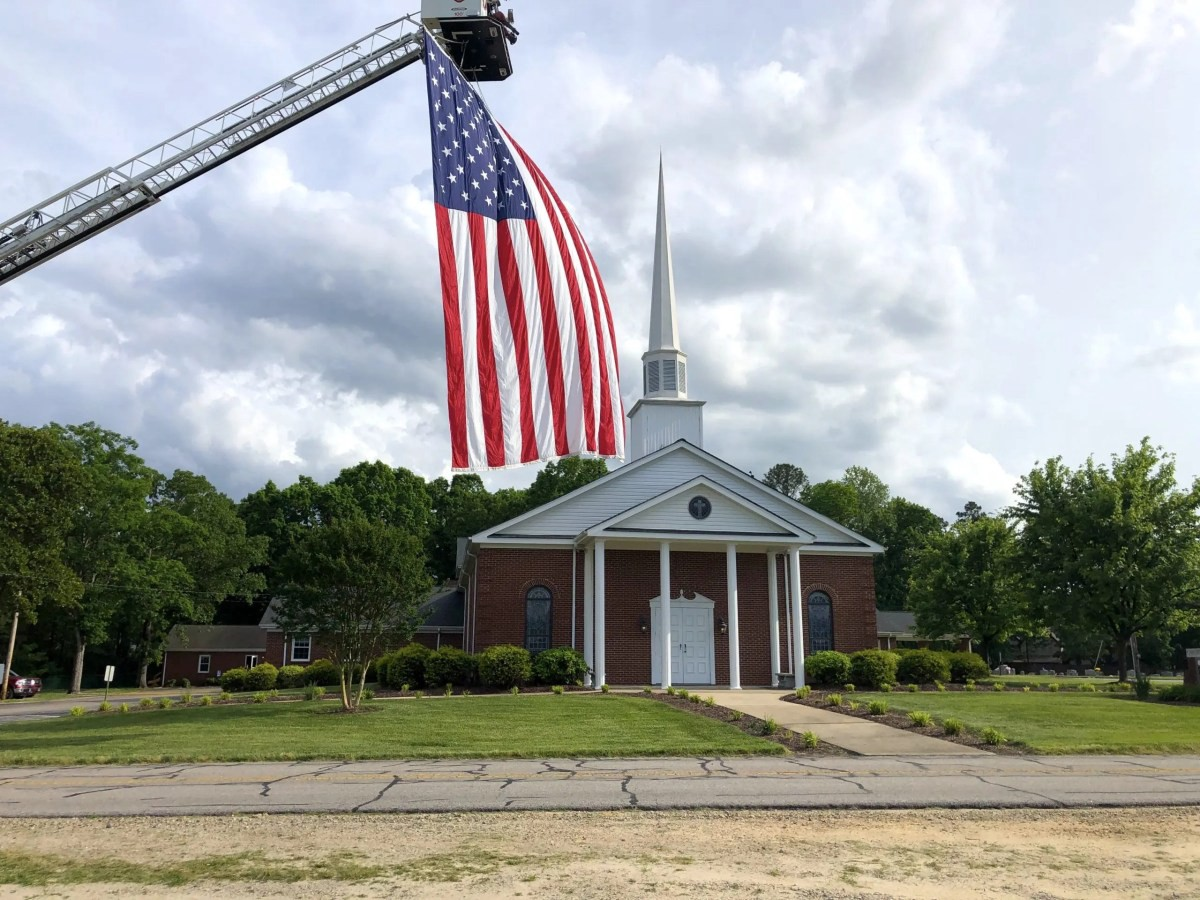 The large American flag hangs from a Wake Forest Fire Department fire truck at the church on the day of Kyle Early's funneral.
