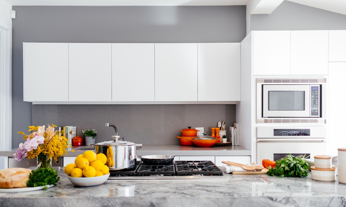 a kitchen with whute cabinets and a grated stove and a marble counter. there is a bowl of lemons on the counter and orange pots and pans