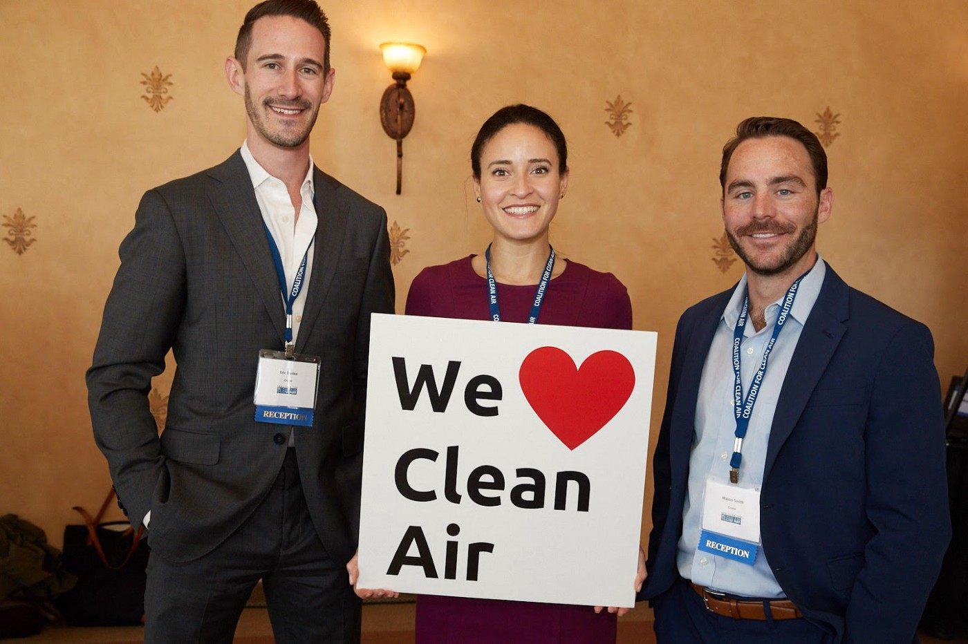 "Eric Danko, Candice Plotkin, and Mason Smith of Cruise pose with a sign that reads, ""We heart clean air."""
