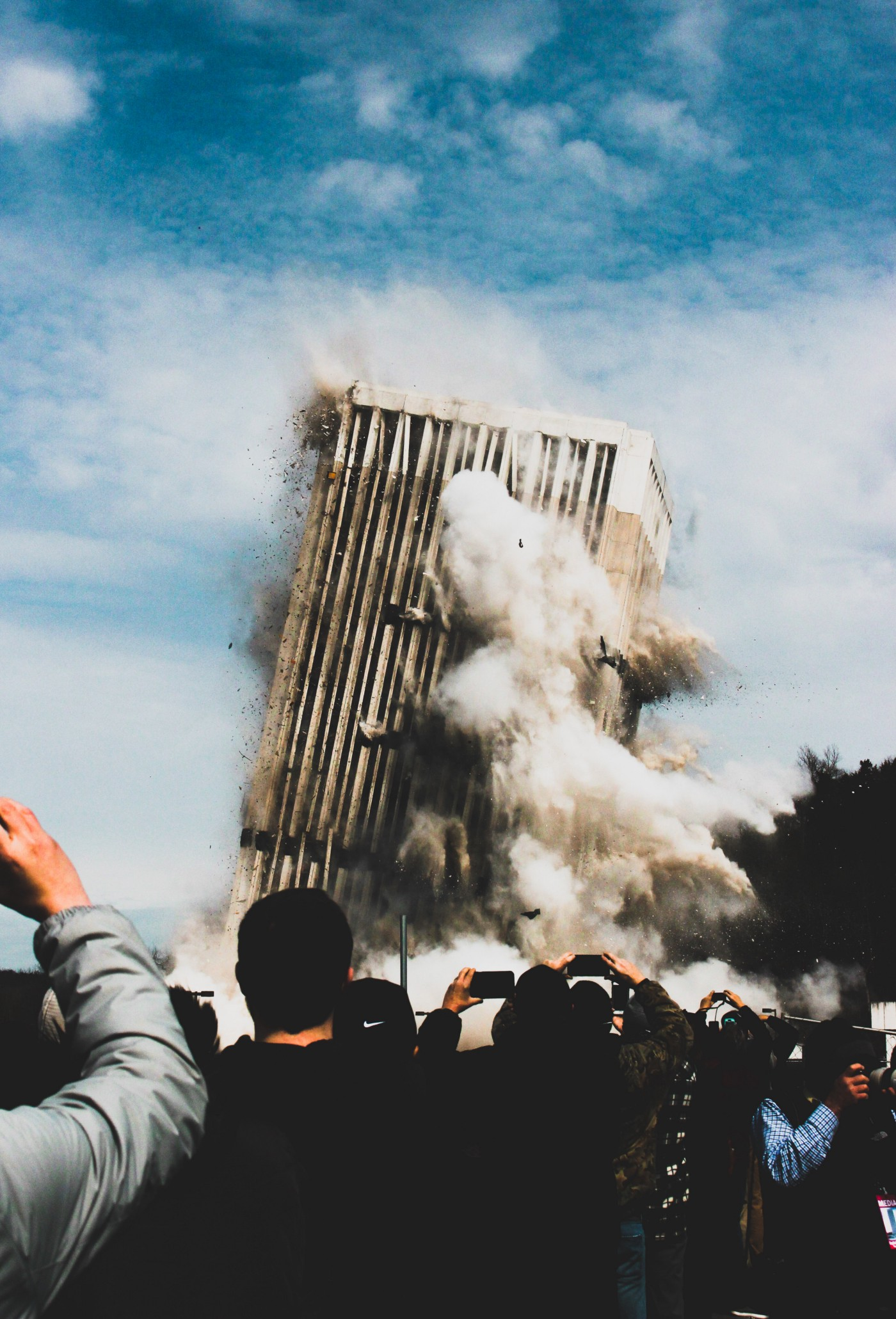 A very tall white building leans to the right with giant plumes of smoke roiling out of it as its foundation collapses underneath it. A building implosion with people's hands holding up cell phone cameras at the bottom as they're taking photos of it.