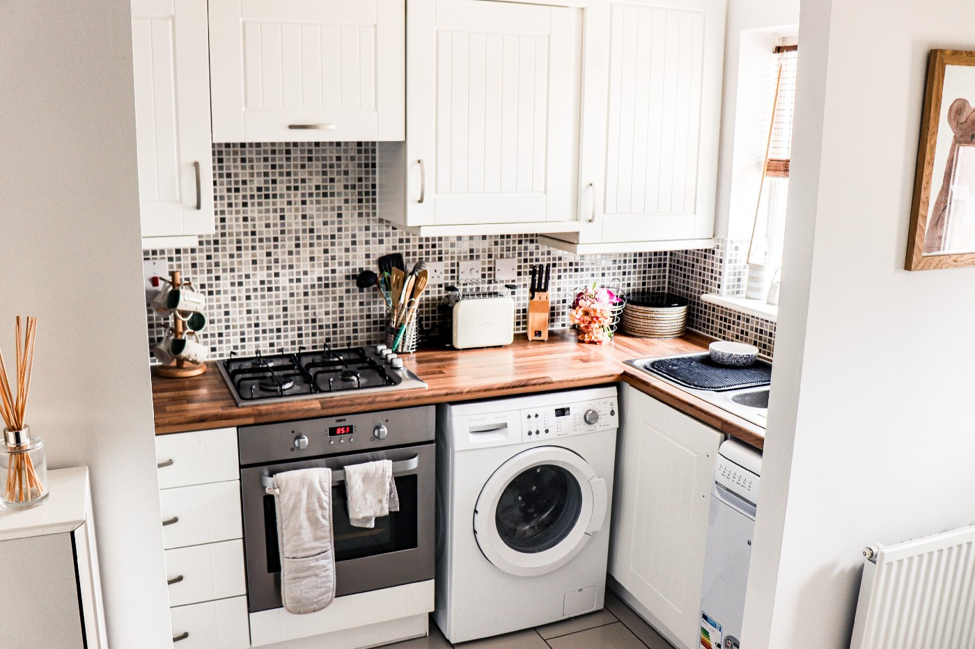 A kitchen, with an oven, washing machine, and cupboards in view.